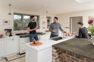 Male friends eating and drinking in modern kitchen fitted with Axiom Thai Beamwood Worktop