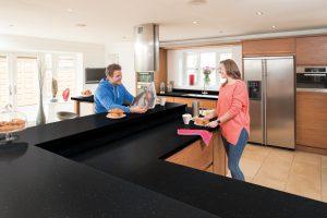 Axiom platinum black laminate worktop, man and woman enjoying breakfast