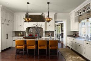 white granite kitchen surfaces with mustard yellow chairs at breakfast bar